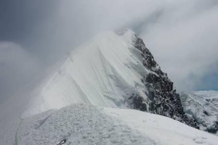 Mot toppen: Brad McMillan skimtes bak skyene, i ferd med å nå toppryggen på Aoraki / Mount Cook. Foto: Andreas Widlund