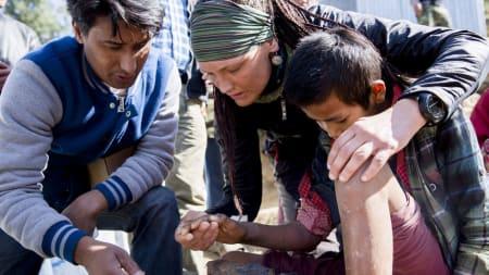 TILBAKE: Vibeke undersøker en 12 år gammel gutt i landsbyen Grang. Han ble skadet under jordskjelvet og har kraftige infeksjoner høyre arm og venstre ben. Foto: Line Hårklau.