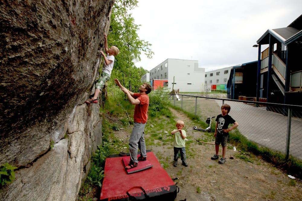 Trym Landmark klatrer på barnehageveggen. Einar Landmark spotter. Foto: Dag Hagen
