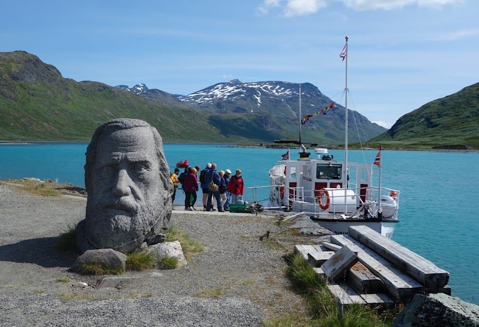 Åsmund Olavson Vinje på Eidsbugarden, med båten og Bygdin bak. Foto: Dag Hagen