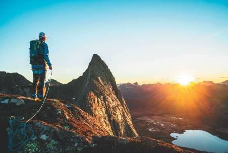 SOLNEDGANG: Marius Birkeland Mo på ryggen med utsikt over Strandåtind før første rappell. Foto: Jarl Gåsvær